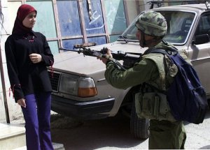 an-israeli-soldier-points-his-gun-at-a-palestinian-woman-in-the-west-bank-city-of-hebron