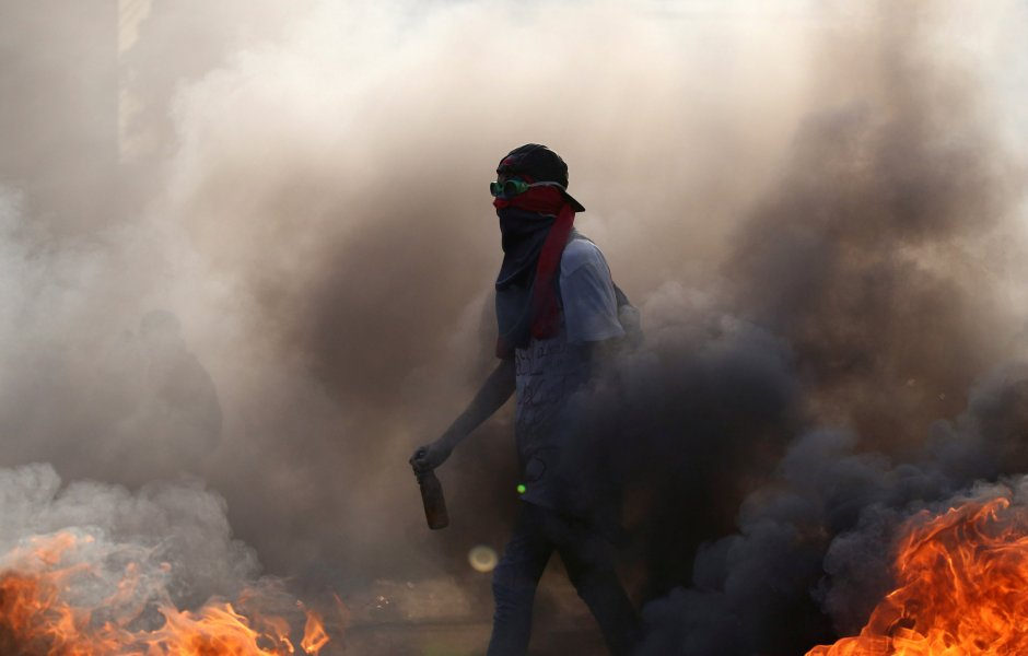 A demonstrator walks while building a fire on the street during a rally in Caracas, Venezuela